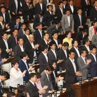 Lawmakers stand up and clap as a bill to allow Emperor Akihito to step down clears the Lower House on Friday. | KYODO