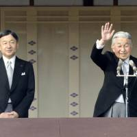 Emperor Akihito, flanked by Crown Prince Naruhito, greets the public at the Imperial Palace on the occasion of his 83rd birthday on Dec. 23 last year. | KYODO