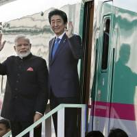 Prime Minister Shinzo Abe (right) and his Indian counterpart, Narendra Modi, wave as they visit Kawasaki Heavy Industries Ltd.'s bullet train plant in Kobe last November. KYODO