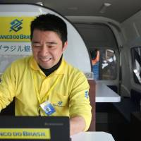 A Banco do Brasil staff member works in the bank's mobile service van in the parking lot of a Brazilian supermarket in Oizumi, Gunma Prefecture, on April 2. | REUTERS