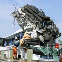 A car that crashed into a bus on the Tomei Expressway in Aichi Prefecture on Saturday is hoisted by crane.  The driver died at the scene. | TOSHIN KANKO BUS CO.