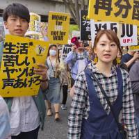 Rie Fujikawa (center) participates in a rally on April 15 in Tokyo's Shinjuku Ward to demand that Japan's minimum wage be hiked to help young people get out of poverty. | KYODO
