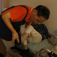 A caregiver helps a resident at a nursing home in Edogawa Ward, Tokyo, in June 2016. The number of people training to become caregivers has dwindled due to an increasing workload and low pay. | BLOOMBERG