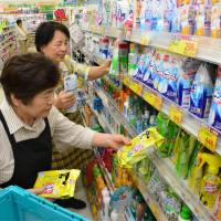 In Kira, Aichi Prefecture, seniors place products on store shelves at an outlet of the Sugi Pharmacy drugstore chain. | CHUNICHI SHIMBUN