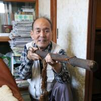 Retired high school teacher Koichi Saito uses a container of arrows to demonstrate how to use a mokuju in this photo taken recently in Tsushima, Aichi Prefecture. | CHUNICHI SHIMBUN