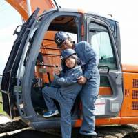 Masato Nakashima, posing with his child, won the award for the most 'likes' in the Macho Photo Contest for Demolition Workers. | CHUNICHI SHIMBUN