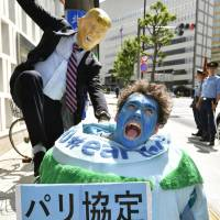Activists protest the U.S. decision to pull out of the Paris climate agreement, outside the U.S. Embassy in Tokyo on Friday. | KYODO
