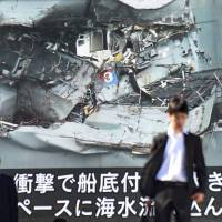 A television news report on the collision between the USS Fitzgerald and a container ship is shown on a big video display in Tokyo on Monday. | AFP-JIJI
