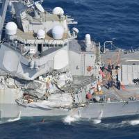 Damage to the right side of the USS Fitzgerald, a guided-missile destroyer, is seen next to its Aegis radar arrays and behind its vertical launch tubes on Saturday following a collision with a Philippine-flagged merchant vessel 56 nautical miles (103 km) southwest of Yokosuka, Kanagawa Prefecture. | KYODO