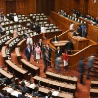 Lawmakers vote on a bill to criminalize conspiracy during an Upper House plenary session on Thursday morning. | KYODO