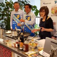 LDP veterans Hakubun Shimomura (center) and Jiro Kawasaki (left) get a taste of cooking duties in a Tokyo studio on Wednesday as they are taught how to make karaage, or deep-fried chicken. | TOMOHIRO OSAKI