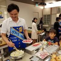 Junior lawmaker Takeshi Ninoyu, who says cooking is his hobby, sets himself apart from other LDP lawmakers by deftly fixing stew for his wife and two little children at an event in Tokyo on Wednesday. | TOMOHIRO OSAKI