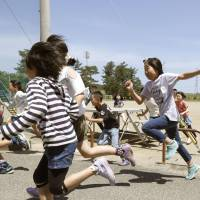 Pupils of an elementary school in Sakata, Yamagata Prefecture, run from a school yard toward a gymnasium during a drill held Friday simulating a North Korean missile attack. | KYODO