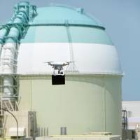 A drone carrying a black box flies near reactor 3 at the Ikata nuclear power plant in Ehime Prefecture on Monday, in the nation's first counterterrorism drill to simulate a drone attack on a nuclear facility. | KYODO