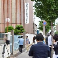 Reporters and camera crews stand in front of the headquarters of Yamamoto Chemical Industry Co. in Wakayama Prefecture on Thursday.   KYODO