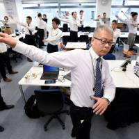 Employees of an IT company exercise together in their office after lunchtime in Tokyo in November. | AFP-JIJI