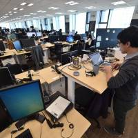 An employee of e-commerce giant Rakuten stands as he works at the office in Tokyo. | AFP-JIJI