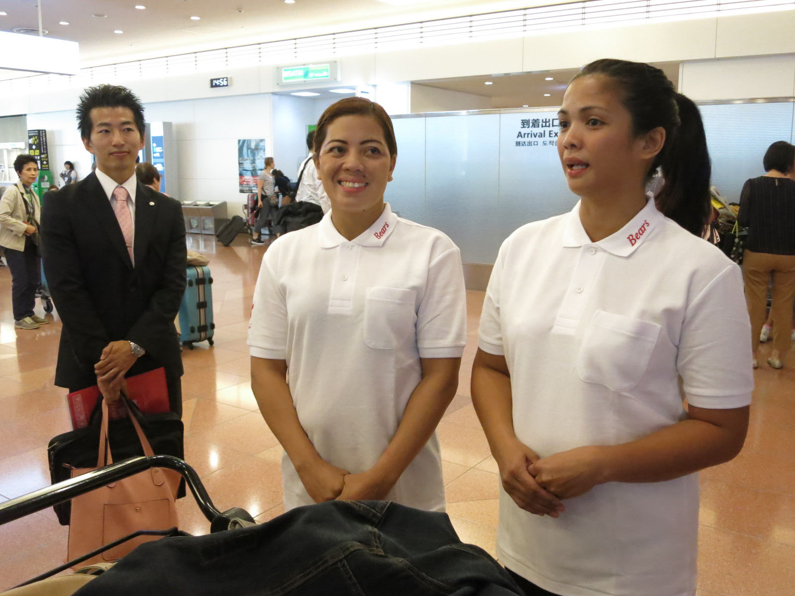 Jocelyn Paloma Oledan (center) and Marianne Paragua Culaniban, who arrived from the Philippines on Wednesday to work as housekeepers in Tokyo, speak to reporters at Haneda airport. | KAZUAKI NAGATA