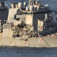 The damaged USS Fitzgerald guided-missile destroyer arrives at its home port in Yokosuka Base, Kanagawa Prefecture, on Saturday. | AFP-JIJI