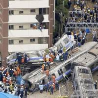 A train on the JR Fukuchiyama Line derailed in file photo taken in April 2005, killing 106 passengers and the driver while injuring 562 in Amagasaki, Hyogo Prefecture. | KYODO
