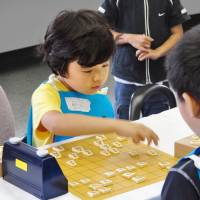 Sota Fujii, seen playing shogi as an elementary school student, started the game when he was 5 years old. | FUJII FAMILY / VIA KYODO