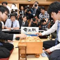 Sota Fujii (right), a 14-year-old professional shogi player, reviews a match with opponent Yasuhiro Masuda, 19, following his win in the prestigious Ryuo Championship finals at Shogi Kaikan hall in Tokyo on Monday night. | KYODO