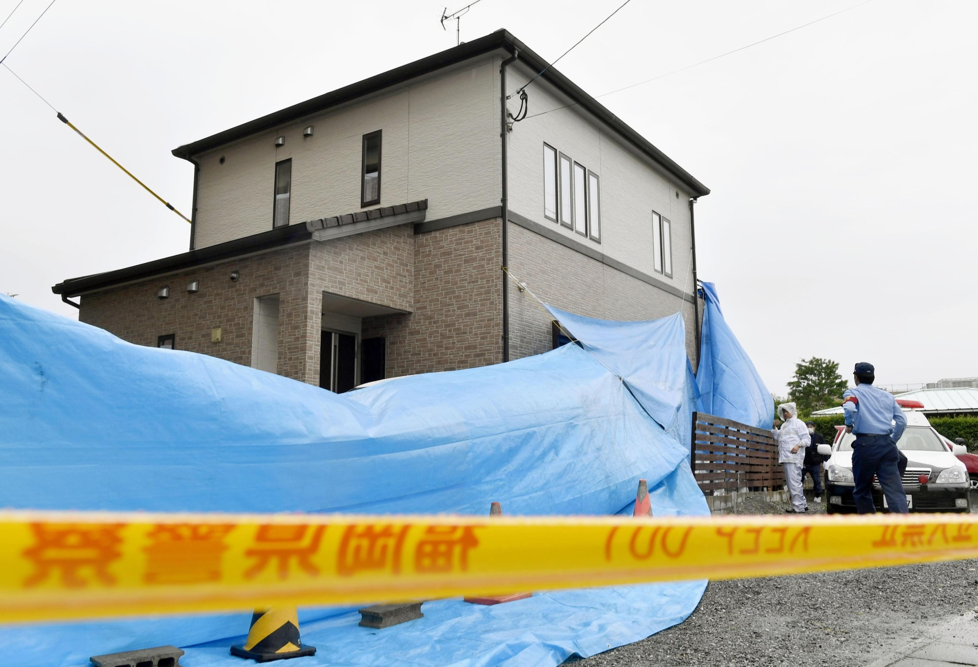 Police Wednesday carry out an investigation at a house in Ogori, Fukuoka Prefecture, where a mother and her two children were found strangled Tuesday. | KYODO