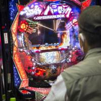 A customer plays pachinko in a Tokyo parlor in May. Japan's thousands of gambling addicts had gone largely unnoticed until a plan to introduce casino resorts forced policymakers to deal with the problem. | BLOOMBERG