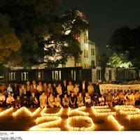 Members of a Hiroshima-based citizens group hold a candle-lighting event in front of Hiroshima Peace Memorial on Thursday to call for the elimination of nuclear weapons. | KYODO