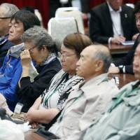 Former residents listen to an announcement last week in Nakashibetsu, Hokkaido, that their trip to the disputed islands off Hokkaido was canceled due to bad weather. | KYODO