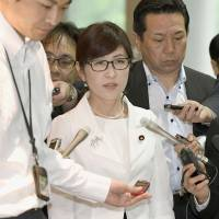 Defense Minister Tomomi Inada is surrounded by reporters as she enters the Defense Ministry in Tokyo on Wednesday. | KYODO