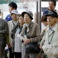 Former residents of the Russian-held islands off Hokkaido listen at Nakashibetsu Airport on Sunday as government officials explain that their flight has been postponed by poor weather.   KYODO