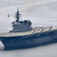 The Maritime Self-Defense Force's Izumo helicopter carrier leaves Yokosuka port in May. The Izumo is now in the South China Sea. | KYODO