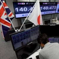 Traders at a Tokyo brokerage check on exchange rates for the British pound on Friday as a TV program reports news that British Prime Minister Theresa May failed to win a majority in the general election. | AFP-JIJI