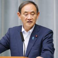 Chief Cabinet Secretary Yoshihide Suga speaks at a news conference on Thursday. | KYODO