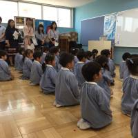 Children at Tokyo Izumi Kindergarten in Adachi Ward meditate while classical music is played in the background as parents look on. | MIZUHO AOKI