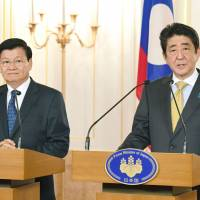 Prime Minister Shinzo Abe (right) and his Laotian counterpart, Thongloun Sisolith, announce joint development plans at a news conference held after a meeting between the top leaders in Tokyo on Wednesday.   KYODO