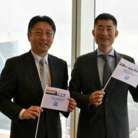 Naosuke Fujita (left), managing director, and Hiroki Inaba, vice president of Goldman Sachs Japan Co.'s legal department, pose with flags they placed in the office to show their solidarity with LGBT employees at the firm's head office in Tokyo. | SATOKO KAWASAKI
