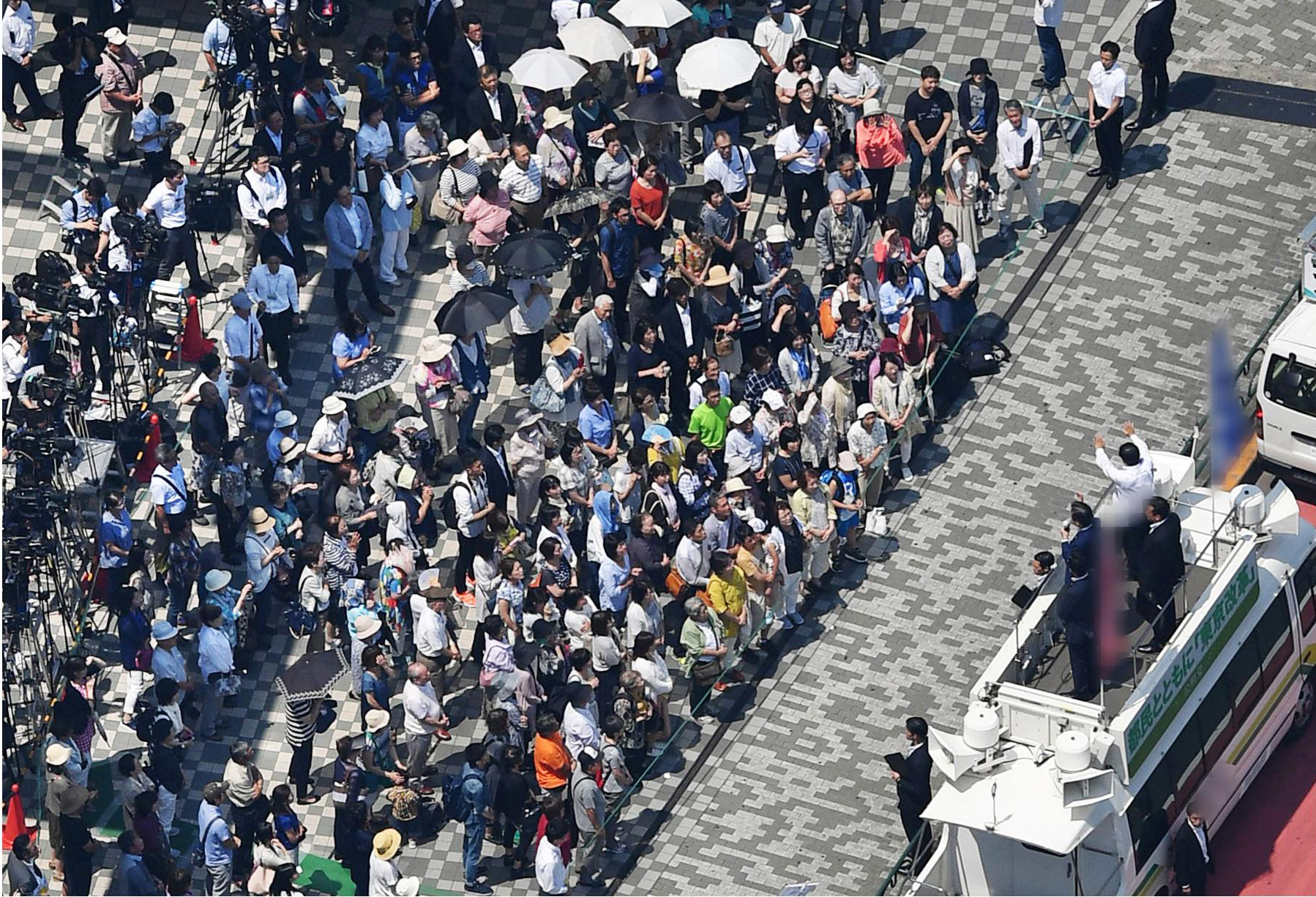 People listen to a politician speak in Shinagawa Ward on Friday morning as campaigning officially kicked off for the July 2 Tokyo Metropolitan Assembly election. | KYODO