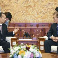 South Korean President Moon Jae-in (right) meets with Toshihiro Nikai, secretary-general of the Liberal Democratic Party, in Seoul on Monday. | KYODO