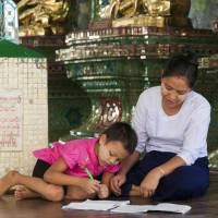A girl does homework with her mother in Yangon. With help from Japan, Myanmar has introduced a new curriculum for first-graders. | KYODO