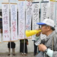 People stage a protest rally in front of Kyushu Electric Power Co.'s office in the city of Saga on Tuesday after a district court rejected an injunction request to halt the restart of two reactors at the utility's Genkai power plant. | KYODO