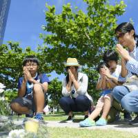 People pray for the victims of the Battle of Okinawa in front of a monument in Peace Memorial Park in Itoman, Okinawa Prefecture, on Friday, the 72nd anniversary of the end of the fierce ground battle. | KYODO
