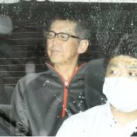 Masaaki Osaka sits in the back seat of a police car after he was served with a fresh arrest warrant on Wednesday in Osaka. | KYODO