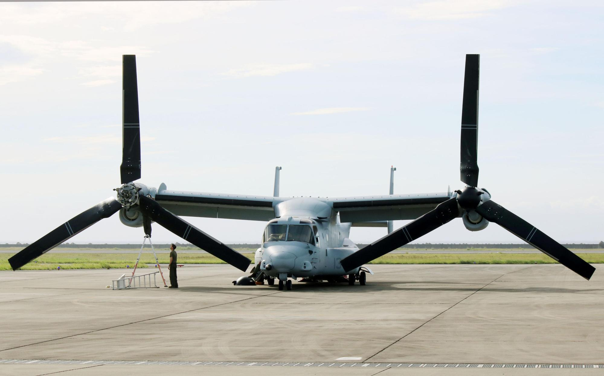 A U.S. Marine Corps Osprey sits on a runway at Amami airport in Kagoshima Prefecture on Sunday after making an emergency landing a day earlier. | KYODO