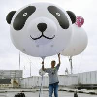 Panda balloons are lifted into the air above a Tokyo department store on Tuesday. | KYODO