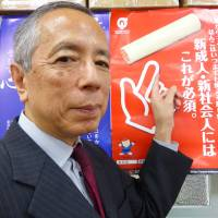 Shoichi Nakajima, representative director of a national association of seal makers and retailers, poses in front of a poster promoting personal seals at the organization's office in Tokyo's Chiyoda Ward on May 24. | SHUSUKE MURAI