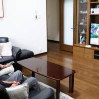A Tokyo couple look at images of their grandchild through the Mago Channeru (Grandchildren Channel) service provided by Tokyo-based startup Chikaku Inc.   KYODO