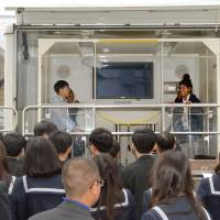 High school students from foreign countries experience a strong jolt generated by a quake simulator in Yuasa, Wakayama Prefecture, last November. | KYODO