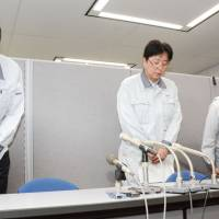 Japan Atomic Energy Agency officials bow Tuesday at a news conference after five workers at its facility in Ibaraki Prefecture were found to have their gloves and shoes exposed to radioactive materials. | KYODO